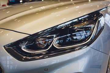 Close up of headlight detail of modern luxury car with projector lens for low and high beam. Front...