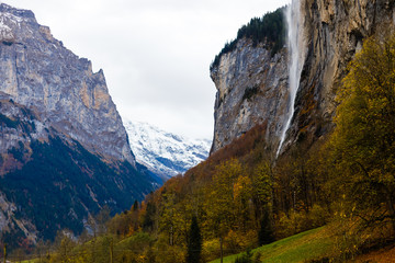 Wall Mural - Beautiful autumn time at village of Lauterbrunnen in Swiss alps, gateway to famous Jungfrau. Set in a valley featuring rocky cliffs and the roaring, 300m-­high Staubbach Falls