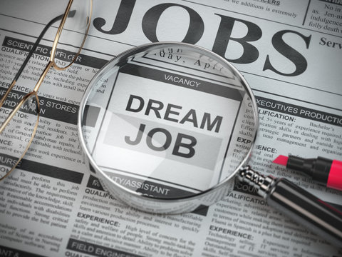 Dream job concept. Job search and employment. Magnified glass with job classified ads in newspaper,