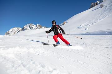 Man skiing on ski piste