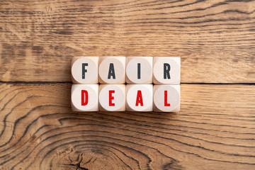 """Würfel mit Aufschrift """"Fair Deal"""" auf Holzuntergrund"""