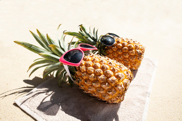 Two Pineapple Lying On Towel Over The Beach