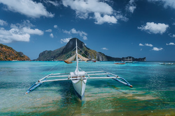 Cadlao panorama with Traditional filippino banca boat in front. Exotic tropical El Nido bay, Palawan Island, Philippines