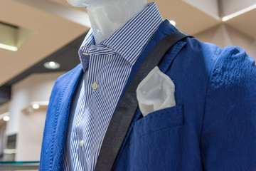 Close up of a mannequin in a fashion store in blue jacket and a white scarf.