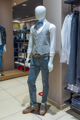 White mannequin in a fashion store with grey vest and blue bow tie.