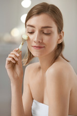 Woman using jade facial roller for face massage at home