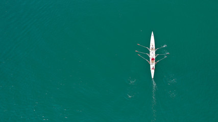 Aerial drone bird's eye view of sport canoe operated by team of young trained athletes in deep blue Aegean sea