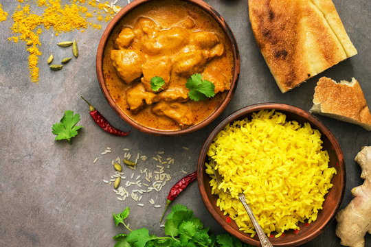 Chicken tikka masala with yellow rice and naan on a dark brown background. Indian food. Top view, copy space, flat lay.
