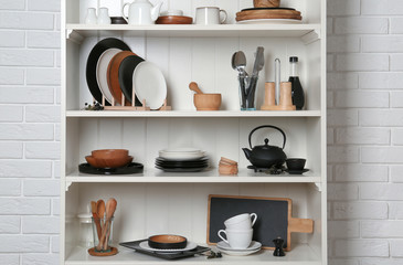 White shelving unit with set of dishware near brick wall