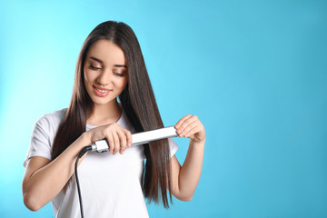Happy woman using hair iron on color background. Space for text
