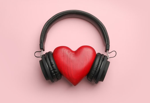 Decorative heart and modern headphones on color background, flat lay