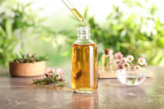 Dripping natural tea tree essential oil into bottle on table