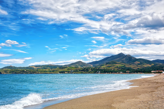 Beautiful deserted beach and mountains on the background. Argeles sur Mer, Roussillon, Pyrenees Orientales, France