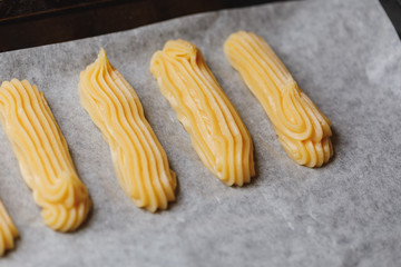 raw eclairs choux pastry on the baking tray