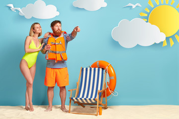 Pleased slim woman with bobbed hairstyle, wears bright green swimsuit, leans at shoulder of lover who has shocked expression, dressed in protective lifejacket, points into distance, pose at beach