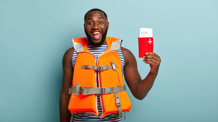 Isolated shot of optimistic ethnic man with broad smile, poses with travel tickets and passport, cares about safety during trip, wears lifejacket, ready for summer vacation isolated on blue background
