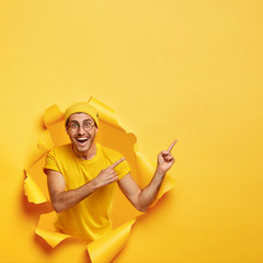 Bright image of happy man has toothy smile, points away on free space, poses in torn paper wall, dressed in casual t shirt and hat, advertises awesome product, isolated over yellow background