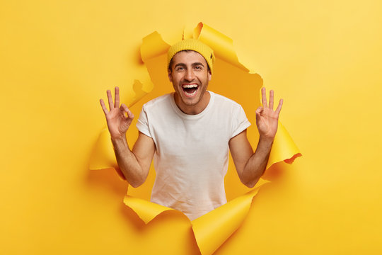 No problem concept. Happy carefree assured Caucasian man with cheerful facial expression, assures everything goes excellent, shows okay sign wears yellow hat and white t shirt, stands in paper hole.