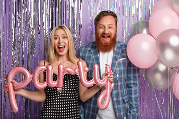 Positive husband and wife organize party with friends, hold air balloons, wear festive outfit,...