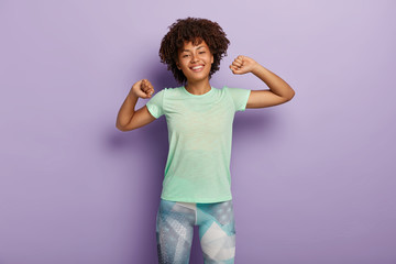 Half length shot of happy young Afro American woman stretches hands, does morning exercises with good mood, wears casual t shirt and leggings, has broad smile, isolated over purple background