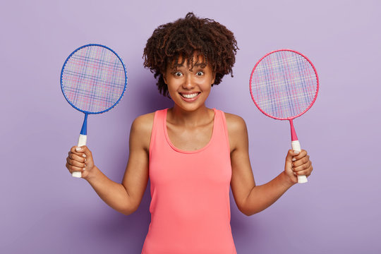 Joyful Afro American woman holds two tennis rackets, invites join her and play game, rests between tennis matches, dressed in sports clothes, has glad expression, stands against purple background