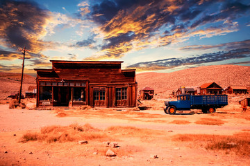 wooden abandoned house with car in the desert at sunset Wall mural