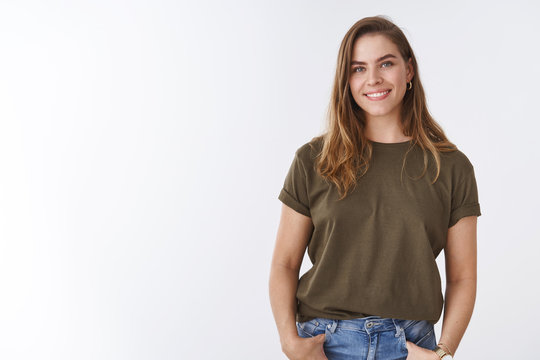 Attractive modern young urban woman chestnut short haircut wearing olive t-shirt holding hands pockets smiling friendly relaxed sound-minded pose, outgoing woman communicating grinning