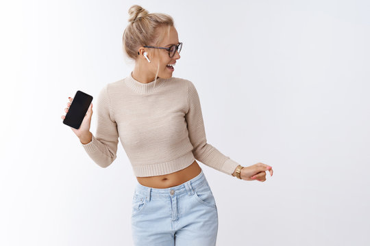Incredible sound. Indoor shot of amused and enthusiastic charismatic blond elegant woman dancing in wireless earphones holding smartphone listening music and enjoying singing along