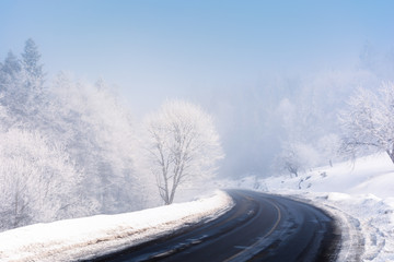 road turn in to the forest in winter. amazing foggy weather. trees in hoarfrost. roadside covered with high snow. cold and bright forenoon. deceptive nature beauty concept. keep your eyes on the road