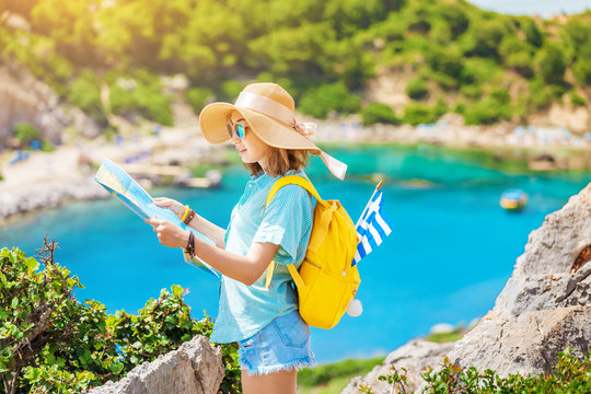 Girl traveler with map looking for interesting places near the blue lagoon bay on the Greek island of Rhodes