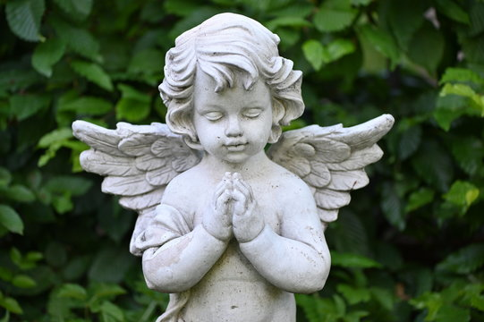 A white sandstone sculpture of a praying angel.