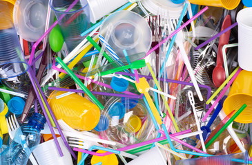 Fototapeta Disposable single use plastic objects such as bottles, cups, forks, spoons and drinking straws that cause pollution of the environment, especially oceans. Top view. obraz