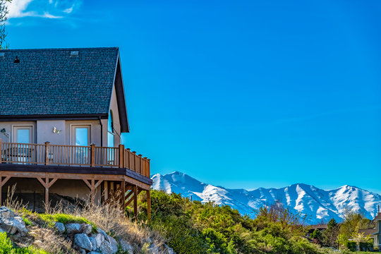 House on a hill with balcony overlooking snowy mountain and bright blue sky