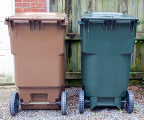Brown and green trash cans in urban neighborhood alley.