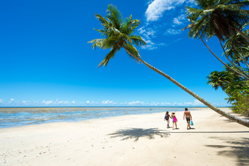 Figures walking under a palm tree leaning out over a wide empty beach on a remote tropical island in Bahia, Brazil Wall mural