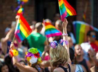 Sunny scenic view of gay pride parade with unrecognizable people waving rainbow flags