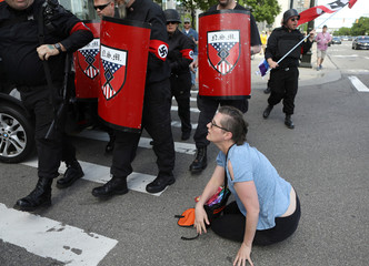 A woman who tried to block the path of members of the National Socialist Movement is shoved to the ground as they demonstrate against the LGBTQ event Motor City Pride in Detroit