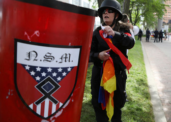 A member of the National Socialist Movement tears apart a pride flag during a demonstration against the LGBTQ event Motor City Pride in Detroit