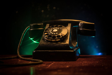 old black telephone on old wood plank with art dark background with fog and toned light. empty space