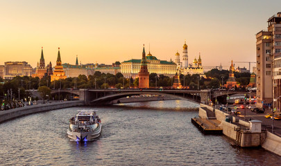 Fototapete - Moscow Kremlin at sunset, Russia. Beautiful view of the Moscow city center in summer. Panorama of famous Moscow Kremlin and Bolshoy Kamenny Bridge. Moscow cityscape with tourist ship on Moskva River.