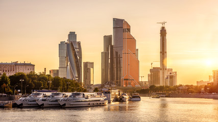 Fototapete - Panorama of Moscow with modern skyscrapers of Moscow-City at sunset, Russia. Sunny view of Moskva River and moored tourist ships in the Moscow center in summer. Moscow cityscape with tall buildings.