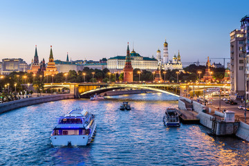 Fototapete - Moscow Kremlin at night, Russia. Beautiful view of the Moscow city center in evening. Panorama of famous Moscow Kremlin and Bolshoy Kamenny Bridge. Moscow cityscape with tourist ships on Moskva River.