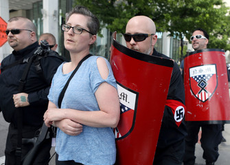 A woman tries to block the path of members of the National Socialist Movement as they demonstrate against the LGBTQ event Motor City Pride in Detroit