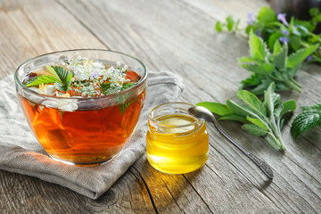 Healthy herbal tea cup, honey jar and medicinal herbs on old wooden table.
