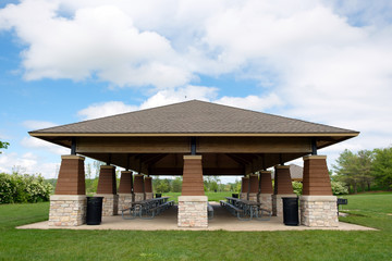 Covered picnic area and tables in public park on sunny day