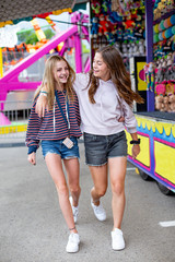 Candid photo of two cute and smiling teenage girls having fun at an outdoor carnival or theme park. Teenagers enjoying their summer vacation.
