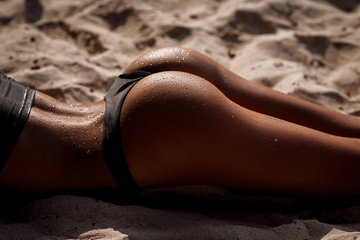 Close-up sexy wet ass of sporty girl wearing black swimsuit at the beach. Part of women body. Tanned booty of young model in bikini.