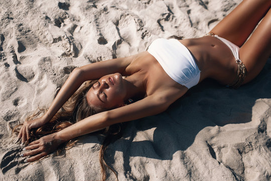 Close up top view of a tan sexy woman lying on sand relaxing on beach.
