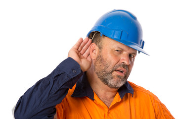 An industrial worker with hearing loss trying to listen.
