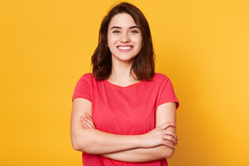 Indoor shot of magnetic beautiful young girl standing with folded arms, looking directly at camera, having sincere smile on her face, posing straight isolated over yellow background in studio.